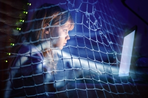Little girl working on laptop at night in a fishing net, Internet addiction disorder conceptual photo collage