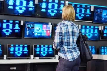 Blonde girl looks at TVs in supermarket